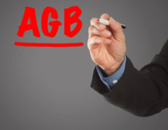 "Male hand in business wear holding a thick pen, writing German term ""AGB"" (terms & conditions in Germany)"